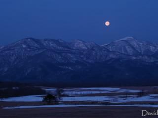 山の向こうに沈む満月