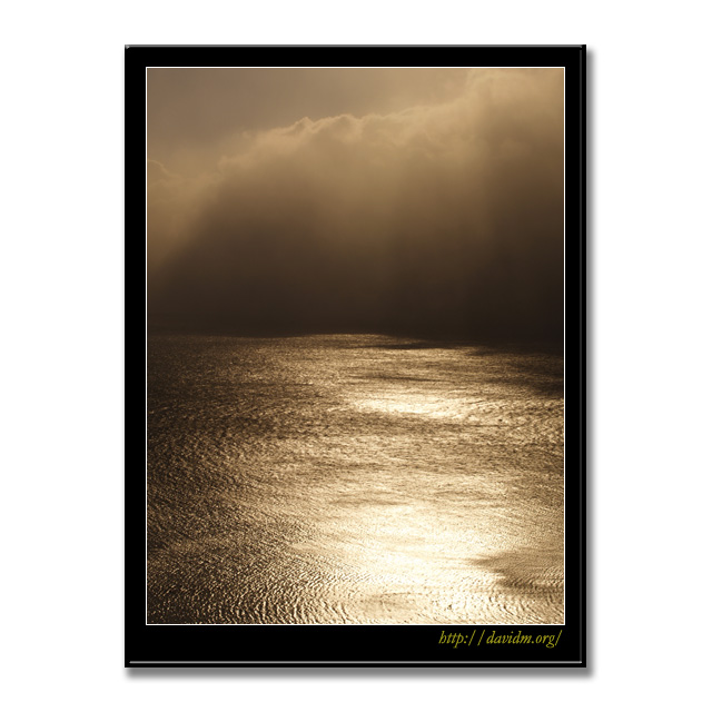雲間の光に照らされる波紋