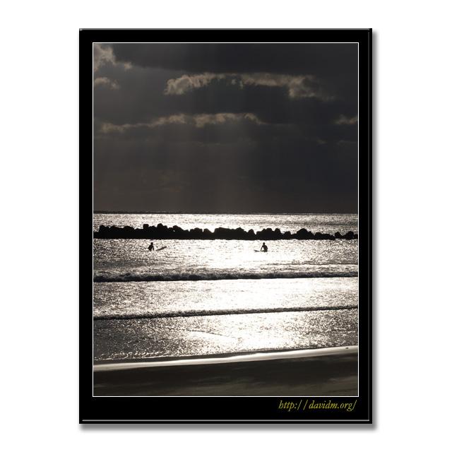 朝の光の中で波を待つサーファー