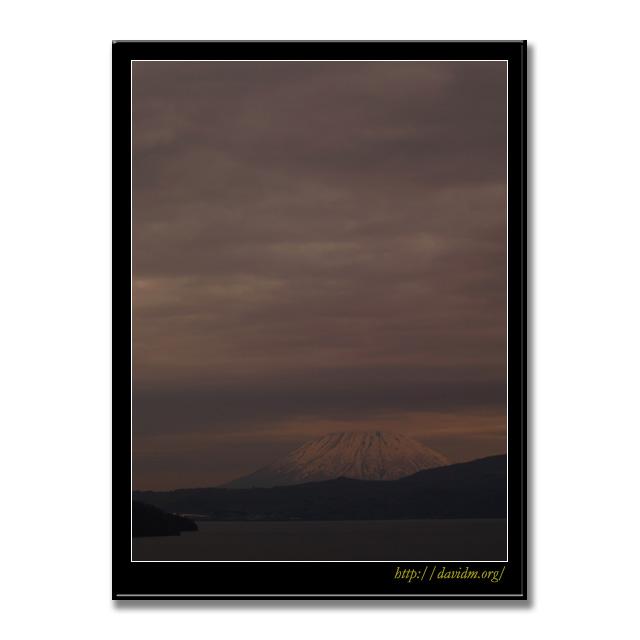 低い雲に光る冠雪した羊蹄山
