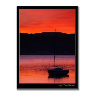 洞爺湖の湖面に映った燃える空に浮かぶヨット