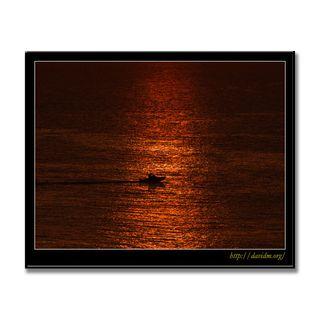 夕陽の道を横切る小さな船
