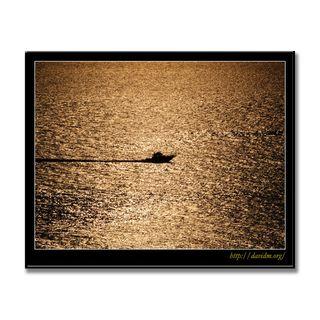 夕陽を横切る釣り船