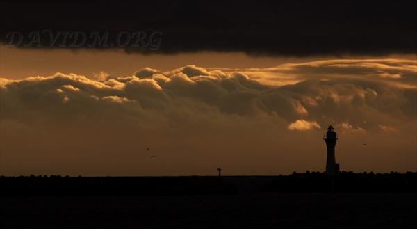 夕陽に染まる雲と灯台の写真